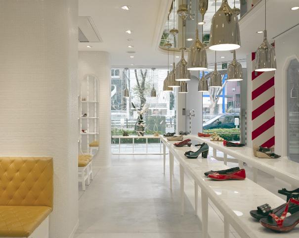 Interior de la botiga a Tòkio amb la taula expositor de sabates llarga.  Al fons una prestatgeria per una peça de porcelana de Jaime Hayón, i a l'esquerra es poden veure dos tamburets. Fotografia de Nienke Klunder.