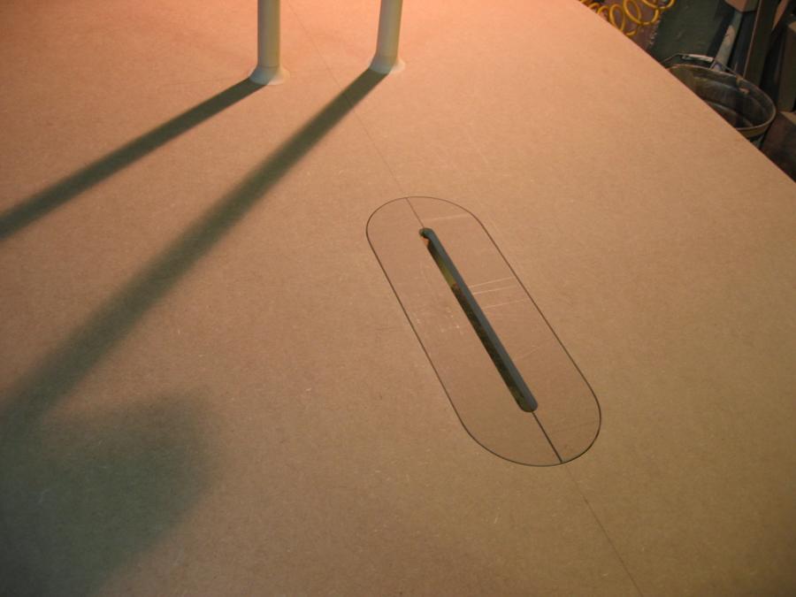 Vista de la superficie de la taula amb la ranura per cables i tapa del contenidor de bateries d'ordinadors portatils