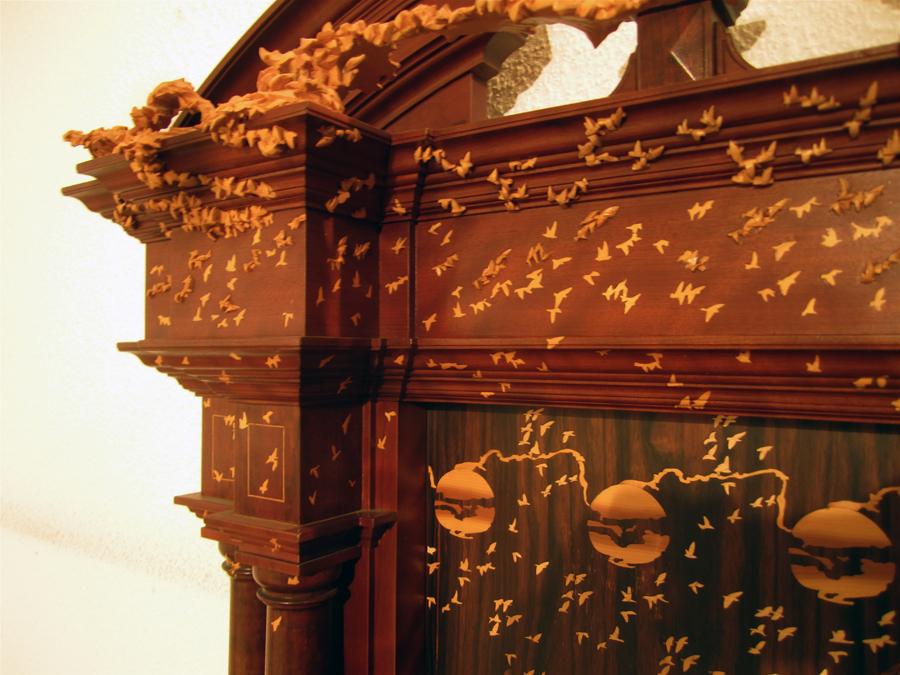 Detall on s'aprecia la fugida dels ocells  de l'interior de la porta a l'exterior, passant de l'imatge plana del plafó de marqueteria al relleu exterior.