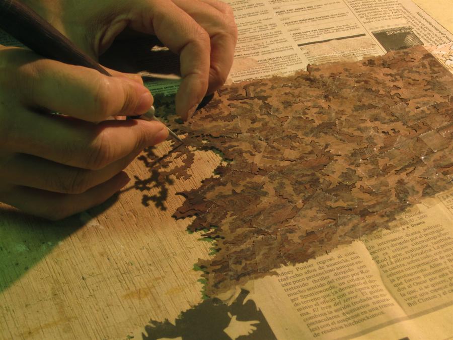 Un cop es tenen les peces de diferents tipus i colors de fusta es el moment de anar ajuntant el trencaclosques que formarà la imatge final.