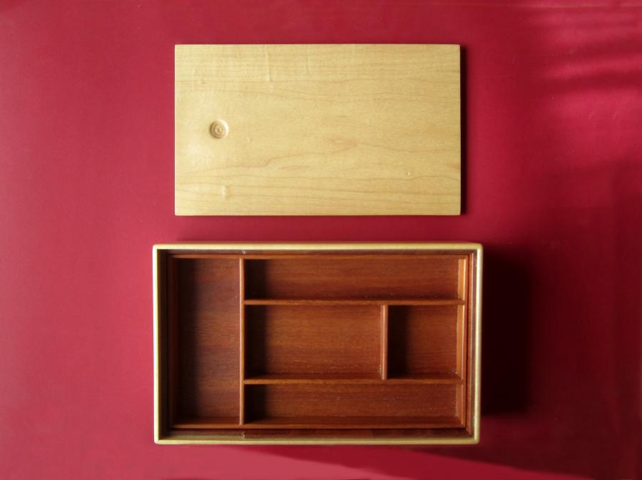 La caixa amb la tapa oberta, es veu la safata de fusta de caoba amb compartiments.