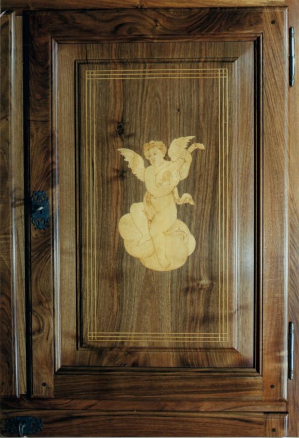 Detall de la porta amb l'àngel music de boix incrustat al plafó de noguera.