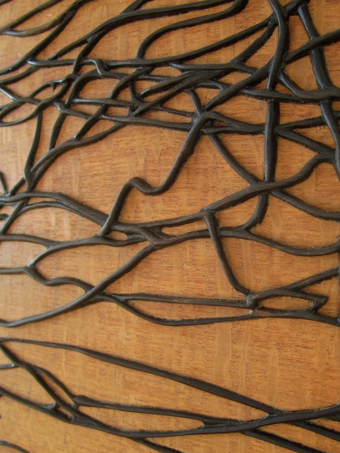 Detall de la fusta de banús tallada en forma de fils embolicats.